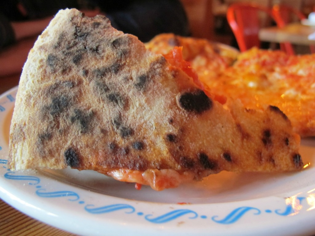 Charred crust on a slice of pizza from Lovely's Fifty Fifty in Portland, Oregon \ vegetarianPDX